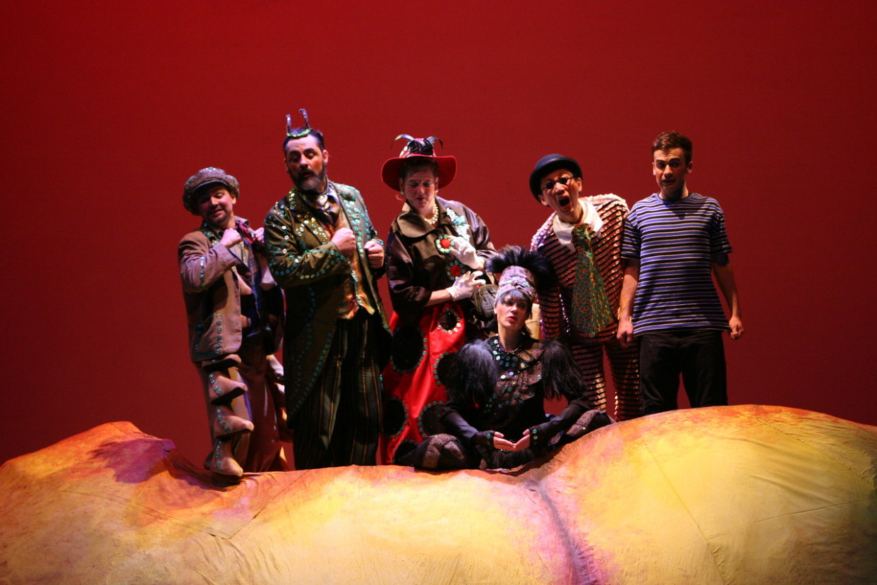 The ensemble from James & the Giant Peach pose on stage in their costumes behind the giant peach set piece.
