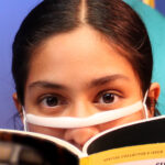 Nivi Varanasi as Vita in HOW TO BUILD AN ARK. PHOTO DESCRIPTION: A youth actor wearing a clear face mask peeks over the pages of a National Geographic magazine.