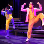 Photo description: Two male actors dance in front of a set of stairs. Their arms are by their heads, bent into a flexed